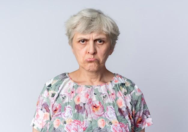 悲しい年配の女性は白い壁に孤立して立っています