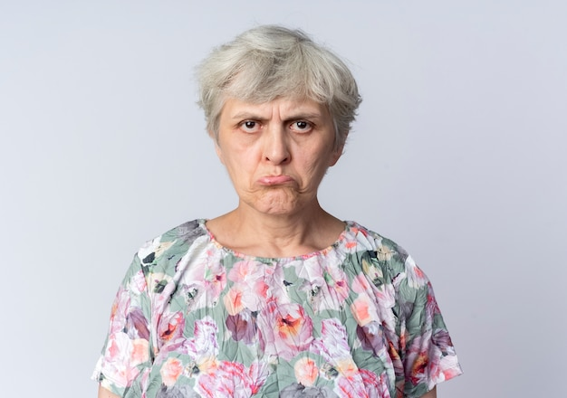 Sad elderly woman stands isolated on white wall