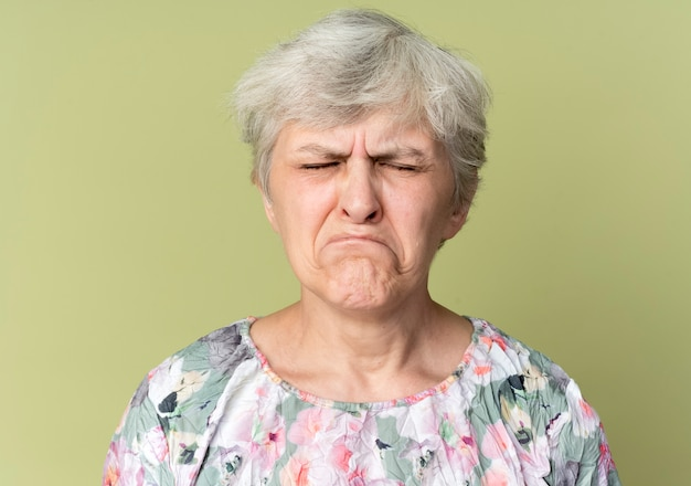 Sad elderly woman stands with closed eyes isolated on olive green wall