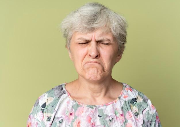 悲しい年配の女性は、オリーブグリーンの壁に隔離された目を閉じて立っています