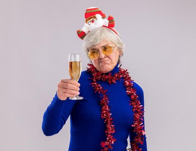 Triste donna anziana in occhiali da sole con santa fascia e ghirlanda intorno al collo tiene e guarda un bicchiere di champagne isolato su sfondo bianco con spazio di copia
