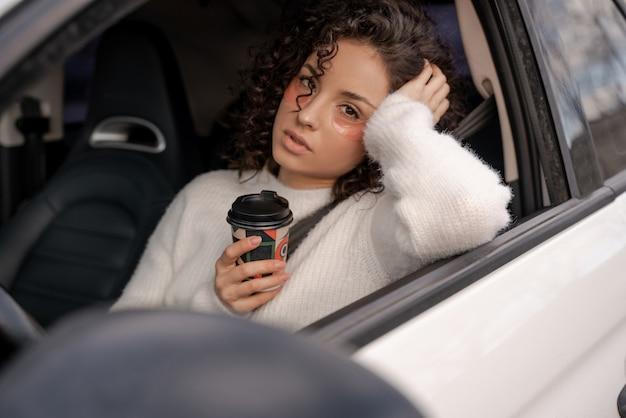 顔に目の下のパッチを持つ悲しいヨーロッパの女の子は、個人の自動車に座っています。コーヒーの紙コップを保持している若い美しい巻き毛の女性。マルチタスク。現代の生活リズム。カメラを見ている人