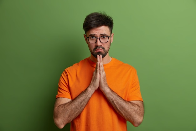 Sad european man with hopeless upset expression prays and has hope for better, guilty look, asks for forgiveness, feels really sorry, presses hands together says please forgive me wears orange t shirt