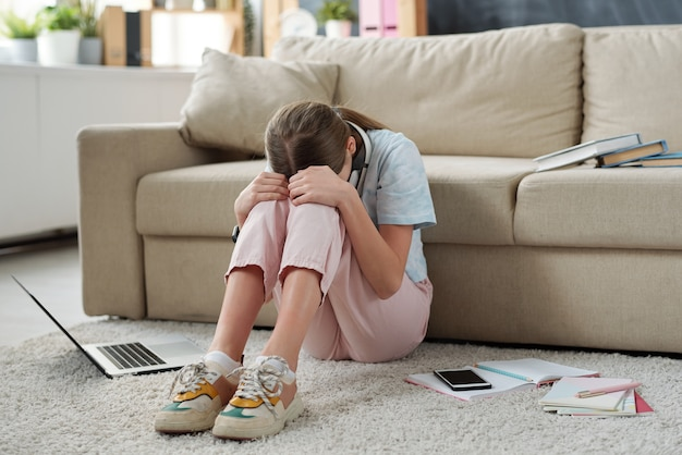 Sad exhausted teenager sitting on carpet with workbooks and crying in living room