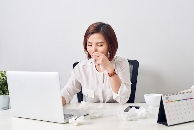テーブルでラップトップで作業中に風邪に苦しんでいる組織を持つ悲しい疲れ果てた女性