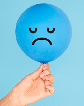 Печальное лицо на воздушном шаре на концепции синего понедельника