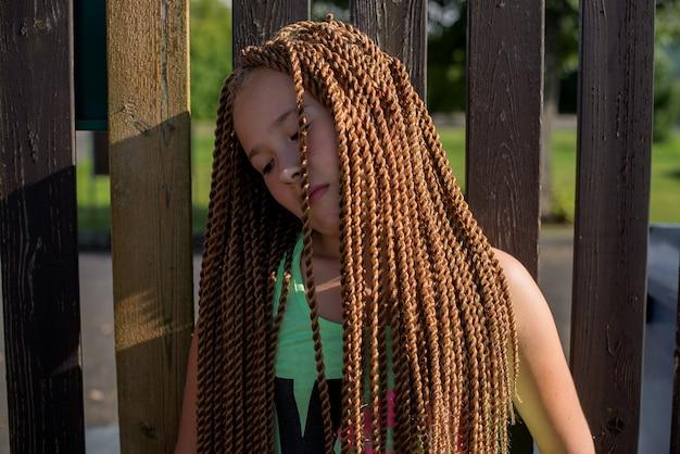 나무 울타리에 서 있는 긴 꼰 머리를 가진 슬픈 얼굴 십 대 소녀