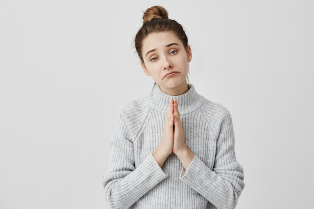 Sad facial expressions of pretty lady with hands together for supplication. female youngster being trendy beseeching parents for money. body language