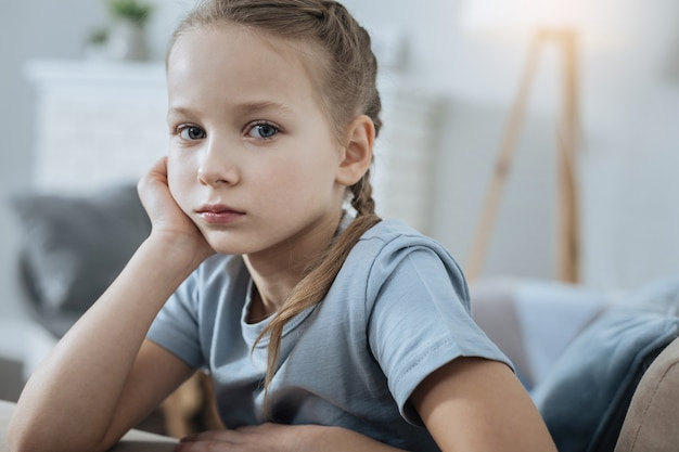 Sad fair-haired blue-eyed little girl thinking and holding her head with her hand while sitting on the sofa