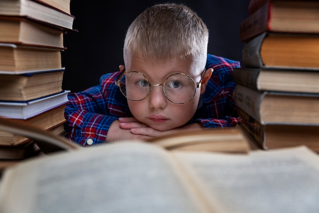 A sad fat boy with glasses sits with books at the table. education and knowledge. close-up.