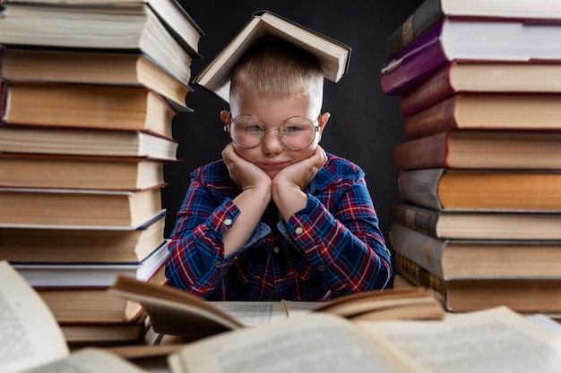 A sad fat boy with glasses sits with books at the table. education and knowledge. close-up. Premium Photo