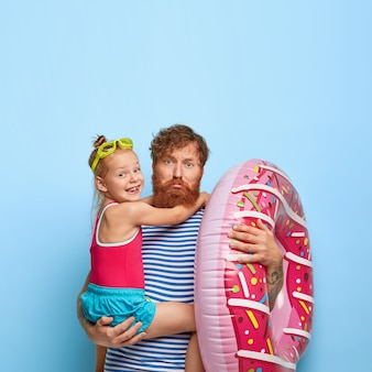 生姜ひげを持つ悲しい疲労の父、手に小さな娘を運ぶ、膨らんだ水泳、一緒にビーチに行く、カジュアルな服を着て、スポーツの場所で楽しませる
