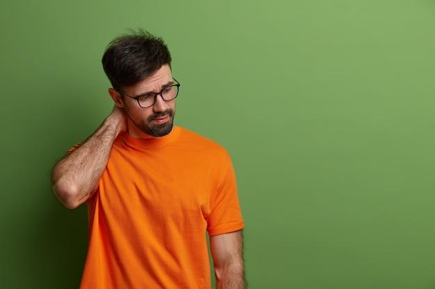 Triste uomo affaticato concentrato verso il basso, tiene la mano sul collo, ha un'espressione premurosa, pensa a come risolvere il problema, è disperato, vestito casualmente, posa su un muro verde vivido, copia spazio