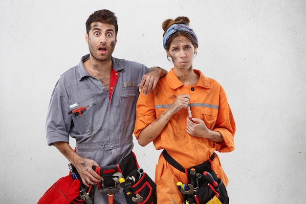 Sad female carpenter holds screwdriver, wears tool belt on waist, stand next to handyman with shocked expression