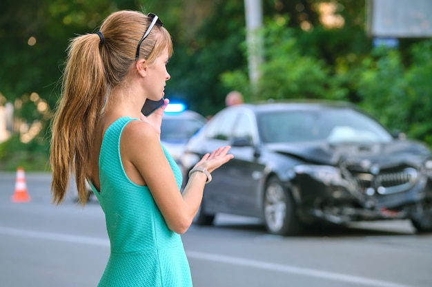 Sad female driver speaking on sellphone on street side calling for emergency service after car accident. road safety and insurance concept.