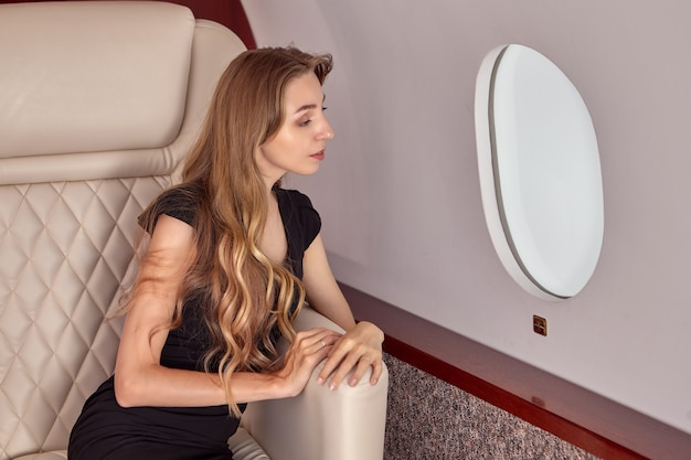 Грустная женщина в пассажирском салоне частного самолета.