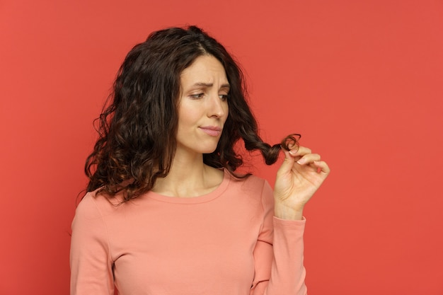 Sad female look at split hair ends curly brunette woman need haircut or professional treatment