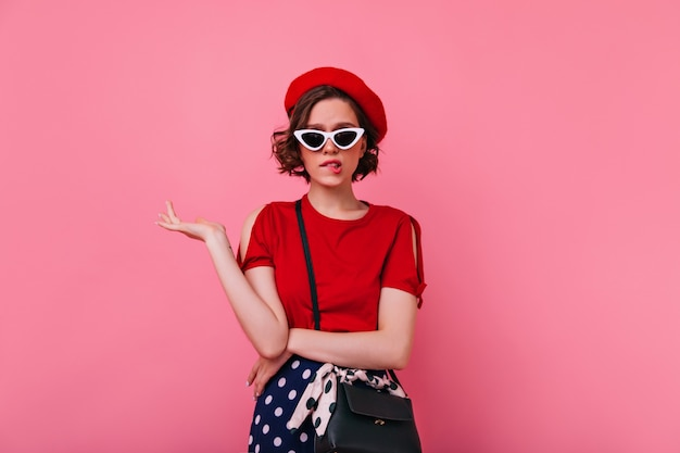 Sad female model in french attire posing. pretty caucasian girl in red beret standing with upset face expression.