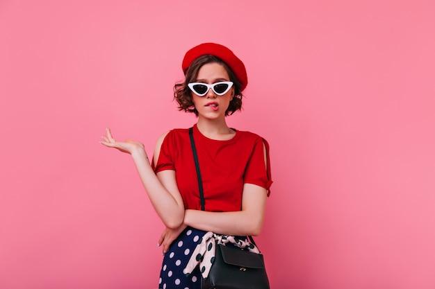 Modello femminile triste in posa abbigliamento francese. ragazza abbastanza caucasica in berretto rosso in piedi con l'espressione del viso sconvolto.