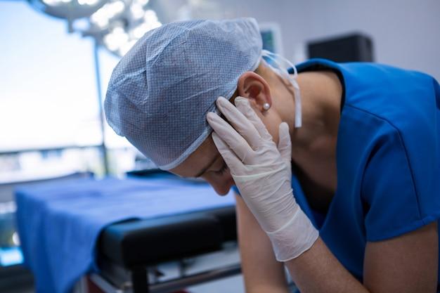 手術室に座っている悲しい女性看護師