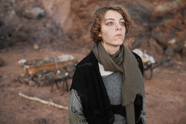 사막에 서있는 동안 멀리보고 찢어진 옷을 입은 슬픈 여성 난민