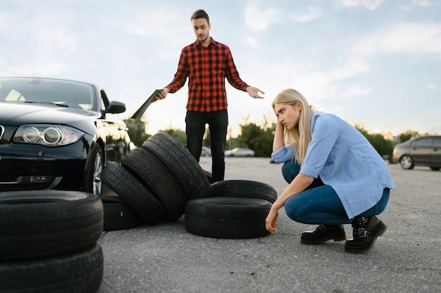 Грустная студентка против подбитых покрышек, урок в автошколе. мужчина учит леди водить автомобиль. образование водительских прав, инструктор и женщина