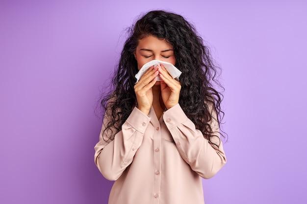 悲しい女性はナプキンで拭き取り、紫色の壁に孤立した叫び声を上げ、鼻をかむ