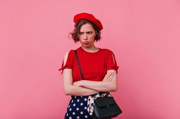 Triste donna francese in abito rosso in posa con le braccia incrociate. modello femminile in berretto in piedi con l'espressione del viso sconvolto.