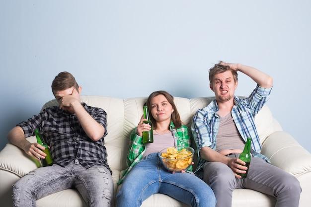 テレビでサッカーを見ている悲しい友達やサッカーファン。お気に入りのチームを失う