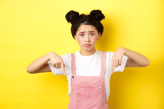 不公平なことに指を下に向け、動揺して暗い顔をして、黄色の化粧をして立っている悲しい眉をひそめているアジアの女の子。
