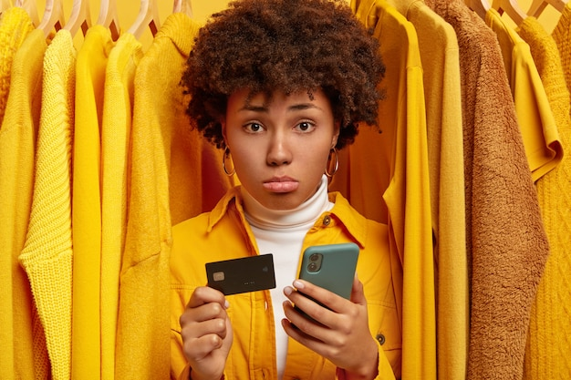 Sad frustrated afro woman makes payment via online wallet, holds credit card and modern cellphone