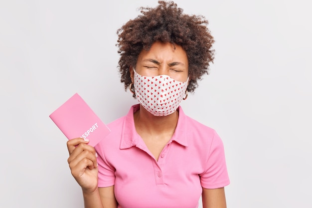Sad frustrated curly haired woman holds passport cannot travel abroad because of coronavirus pandemic and quarantine wears disposable face mask casual pink t shirt isolated over white wall