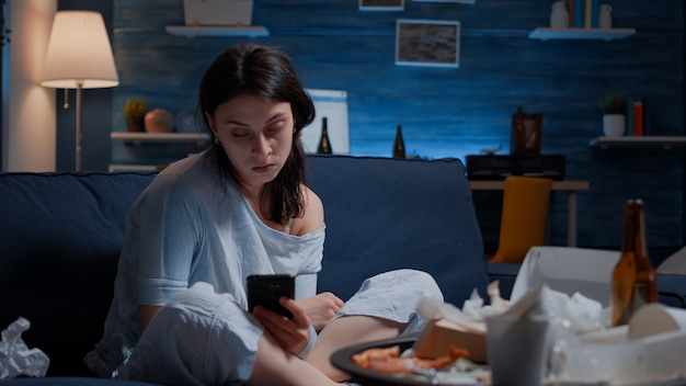 Печальная разочарованная женщина, читающая плохие новости по мобильному телефону, выбрасывающая телефон, нервная, раздраженная, подавленная ...