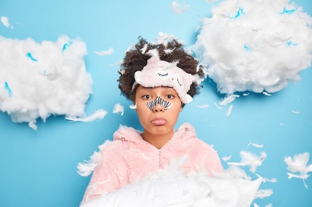 悲しい欲求不満の女性は枕を保持し、周りの羽を目覚めさせた後、寝間着に身を包んだ黒い点を取り除くために鼻パッチを適用します