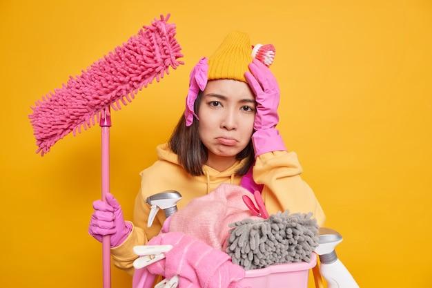 La giovane donna asiatica frustrata triste soffre di mal di testa dopo aver fatto molto lavoro sulla casa odia il bucato tiene la scopa per pulire le pareti della stanza isolata su sfondo giallo esprime emozioni negative