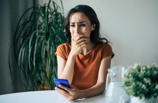 Грустная, разочарованная молодая брюнетка плачет со смартфоном в руках, сидя на стуле в квартире