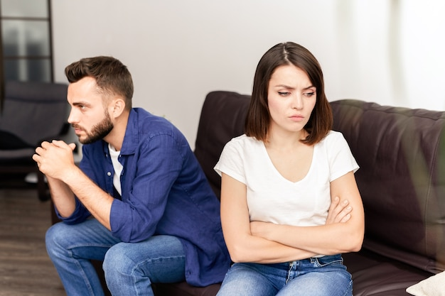 Sad frustrated young couple being in quarrel sitting on sofa in living room and thinking about their problems