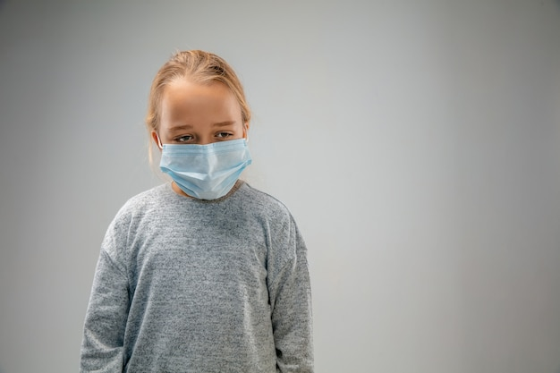 Sad future. caucasian little girl wearing the respiratory protection mask against air pollution and dust particles exceed the safety limits. healthcare, environmental, ecology concept.
