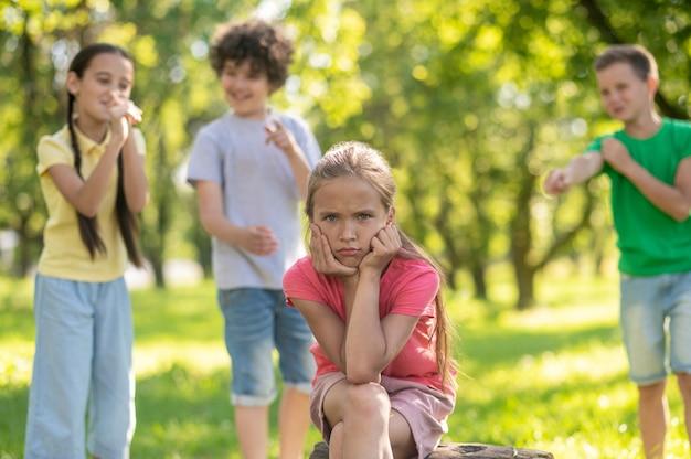 屋外の後ろで嘲笑する悲しい少女と子供たち