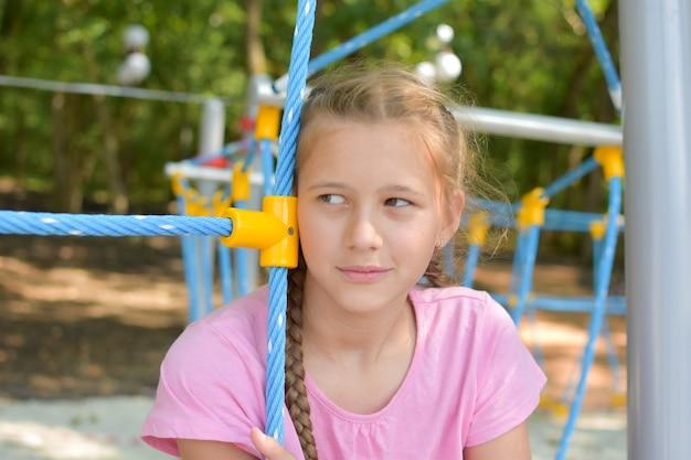 遊び場で悲しい少女。悲しげな子供は思慮深くなりました。孤独