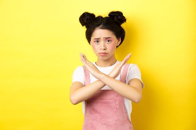 중지를 구걸하는 슬픈 소녀, 눈살을 찌푸리고 십자가 기호를 보여주는, 아니오라고 말하고, 노란색 배경에 우울한 서