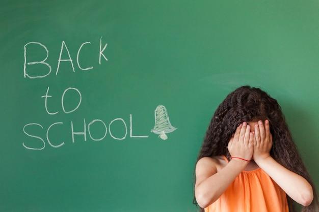 Sad girl at blackboard in classroom