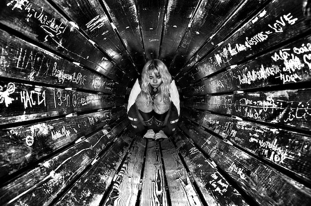 Sad girl at the end of wooden tunnel, white inscriptions carved in wood.