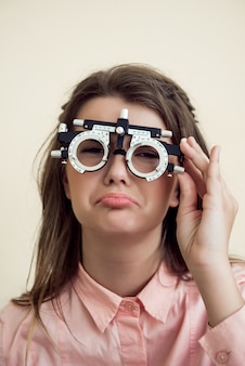 Грустная девушка имеет проблемы с глазами. портрет расстроенной мрачной европейской женщины в кабинете офтальмолога, проверяющей зрение сидя и носящей фороптер, сожалеющей о том, что она испортила зрение возле компьютера
