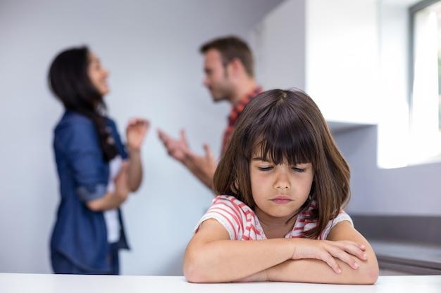 Sad girl hearing her parents arguing