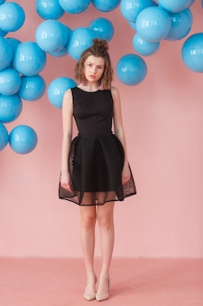 Sad girl in cute black dress on pink background with blue balloons