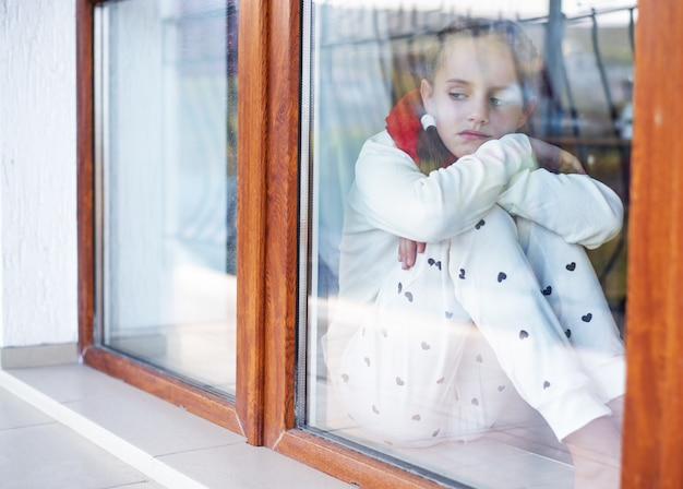 Грустная девушка в пижаме смотрит в окно из дома