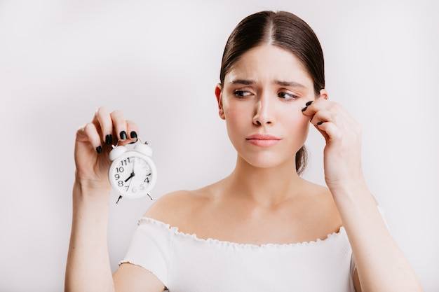 Грустная девушка в белом топе с грустью смотрит на белый будильник. портрет модели без макияжа.