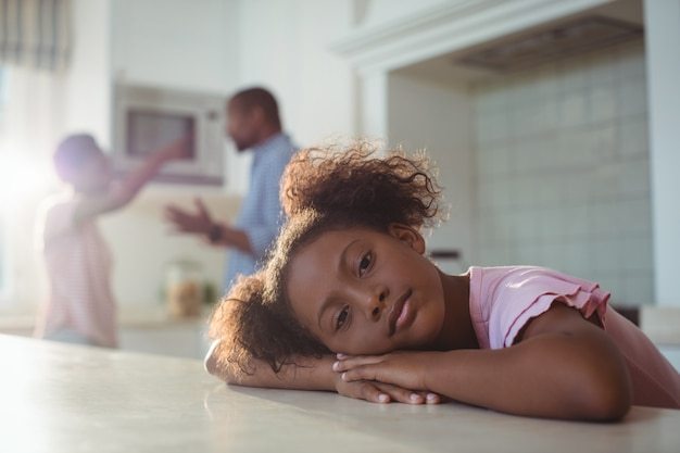 Sad girl listening to her parents arguing in kitchen