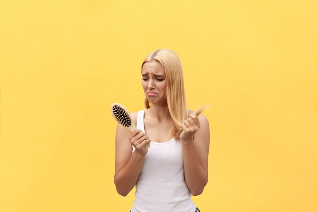 Sad girl looking at her damaged hair with comb in hand